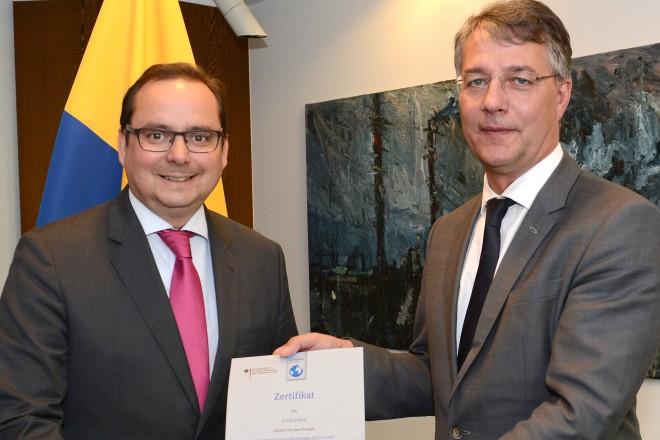 """Staatssekretär Gunther Adler übereicht das Zertifikat über die """" Einsparung von Treibhausgasmissionen """" an Oberbürgermeister Thomas Kufen"""