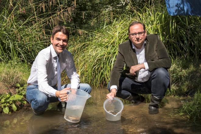 Dr. Uli Paetzel und Oberbürgermeister Thomas Kufen setzen die Emschergroppe in den Borbecker Mühlenbach ein.