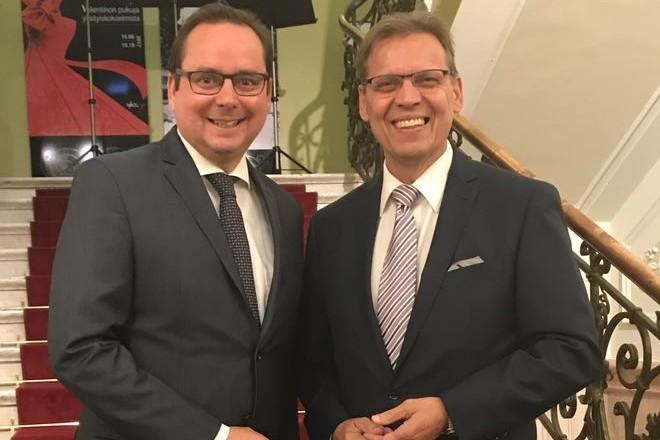 Zwei lächelnde Männer im Anzug auf einer Treppe