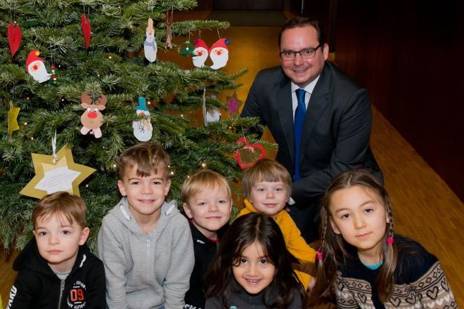 Kinder der Kita Steeler Straße schmücken den Weihnachtsbaum vor dem Büro des Oberbürgermeisters. Darüber freuen sich Oberbürgermeister Thomas Kufen und Sozialdezernent Peter Renzel (links).