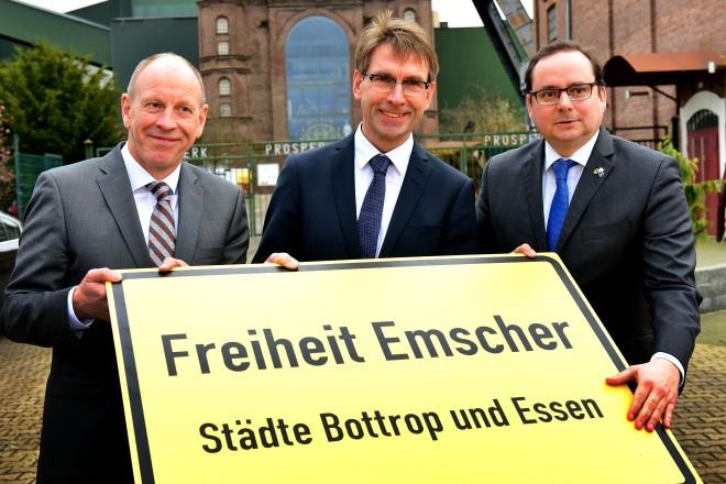 """Thomas Kufen, Markus Masuth und Bernd Tischler halten ein Ortsschild mit der Aufschrift """"Freiheit Emscher. Städte Bottrop und Essen"""""""