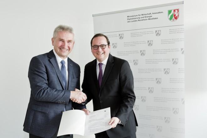 Prof. Dr. Andreas Pinkwart, Minister für Wirtschaft, Innovation, Digitalisierung und Energie des Landes Nordrhein-Westfalen, und der Oberbürgermeister der Stadt Essen Thomas Kufen präsentieren gemeinsam ein Dokument und schütteln sich dabei die Hand. Im Hintergrund befindet sich ein Roll-Up des Ministeriums.
