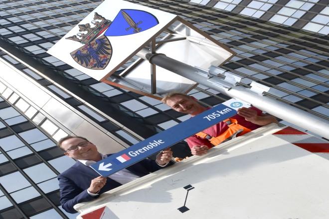 Aufstellen der Wegweiser zu den Essener Partnerstädten Oberbürgermeister Thomas Kufen und Andre Staudinger befestigen das Hinweisschild der Partnerstadt Grenoble