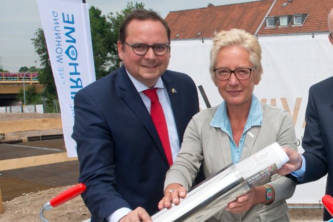 Oberbürgermeister Thomas Kufen (links), Claudia Goldenbeld, Geschäftsführerin von VIVAWEST und Martin Dornieden, Geschäftsführer der FAIRHOME GmbH legten den Grundstein für ein neues Wohnquartier in Frohnausen an der Nöggerathstraße.