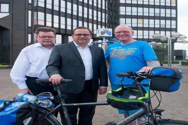 Oli Trelenberg (rechts) radelt für den Wünschewagen. Bei seinem Zwischenstop in Essen empfing ihn Oberbürgermeister Thomas Kufen. Links im Bild Amtsarzt Dr. Rainer Kundt.