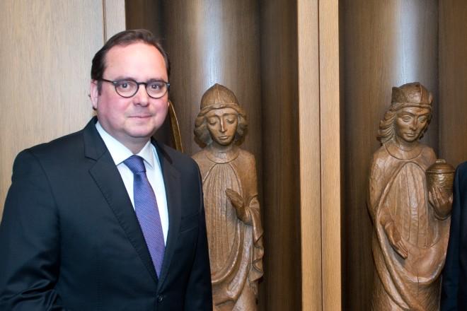 Thomas Kufen, Franz Grave und Veronika Lühl vor Holzplastiken von christlichen Heiligen.