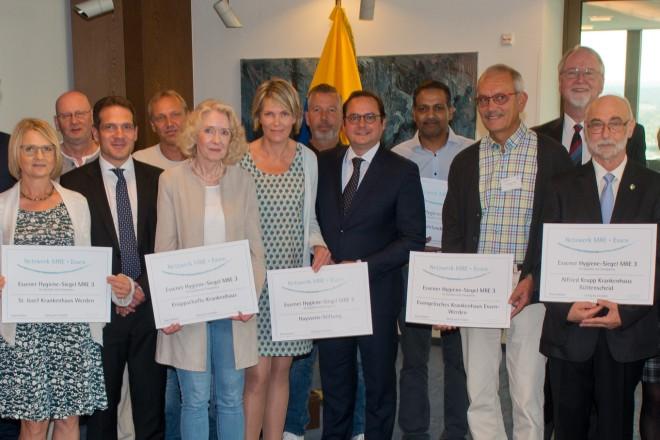 Oberbürgermeister Thomas Kufen (Mitte) überreicht die MRE-Siegel an Essener Krankenhäuser in der 22. Etage des Essener Rathauses.