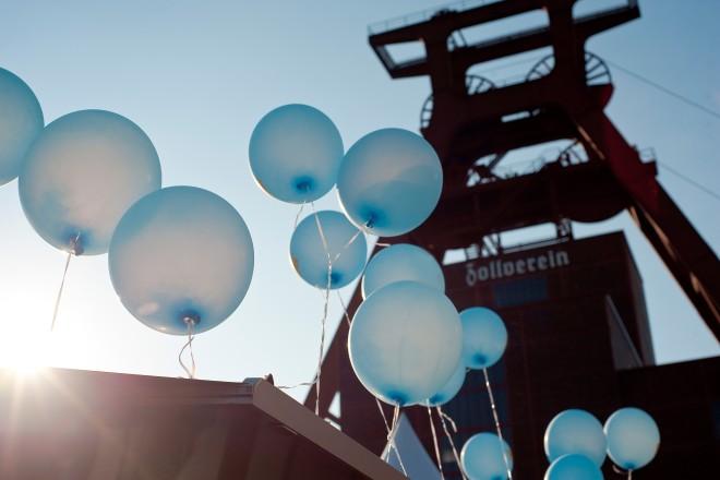 Der Förderturm der Zeche Zollverein. Im Vordergrund fliegen hellblaue Ballons.