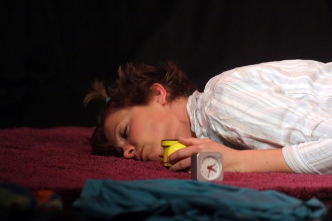 Frau liegt mit Wecker in der Hand am Boden.