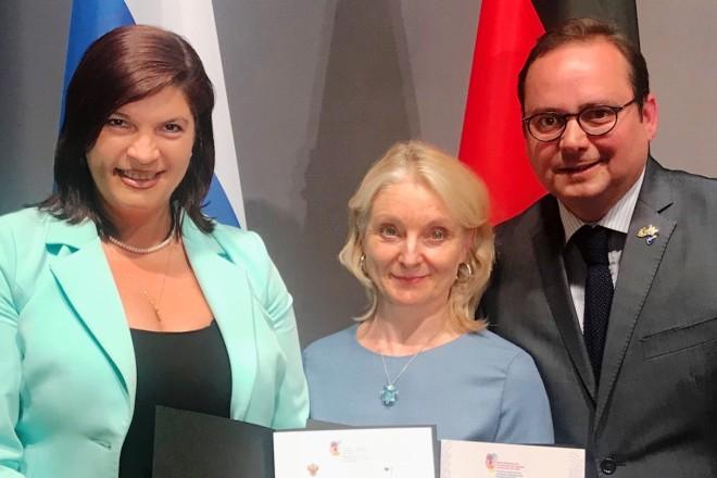 Oberbürgermeister Thomas Kufen mit zwei Damen bei der Übergabe der Urkunde in Berlin
