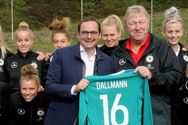 Oberbürgermeister Thomas Kufen und Trainer Horst Hrubesch stehen vor der Damen-Nationalmannschaft.