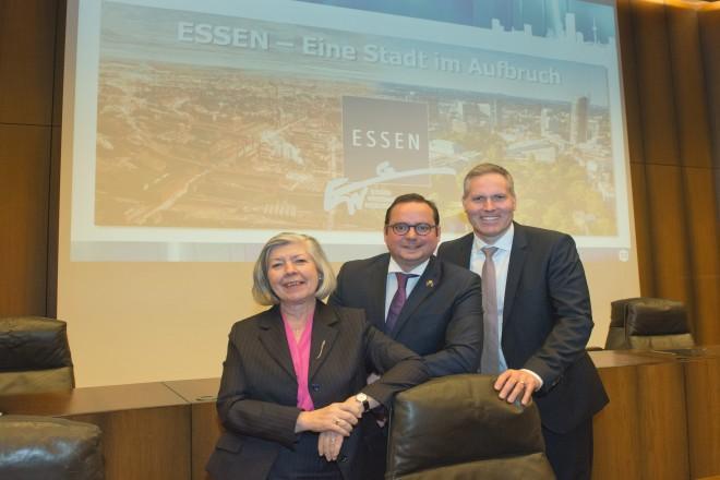 Eine Dame und zwei Herren stehen vor einer Projektionswand mit einem Bild der Stadt Essen