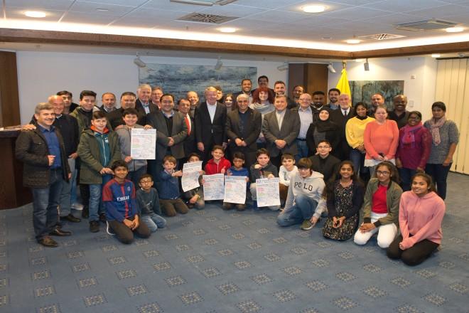 Eine Gruppe Menschen unterschiedlicher Generationen stehen für ein Gruppenbild zusammen. Fünf Kinder halten ein Plakat entgegen