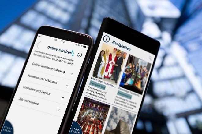 zwei Smartphones zeigen auf Ihren Bildschirmen seiten des Stadtportal Essen to go App. Hinter ihnen sieht man unscharf das Essener Rathausgebäude