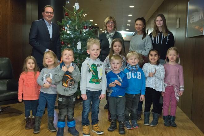 Eine Gruppe kleiner Kinder steht mit vier Erwachsenen vor einem geschmückten Tannenbaum