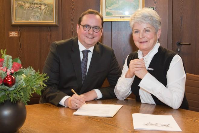 Eine Frau und ein Mann sitzen an einem Tisch. Der Mann ist dabei, ein Schriftstück zu unterzeichnen