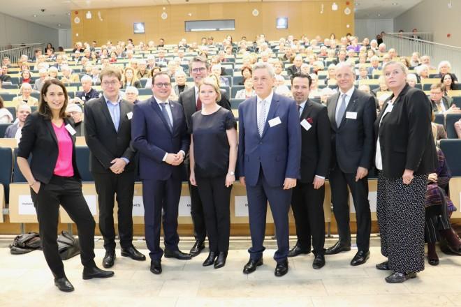 Drei Damen und sechs Herren stehen zu einem gruppenbild zusammen. Hinter Ihnen befindet sich ein voll besetzter Zuhörersaal
