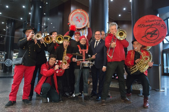 Schwarz-rot gekleidete Leute stehen mit Musikinstrumenten für ein Gruppenbild mkit Oberbürgermeister Kufen zusammen