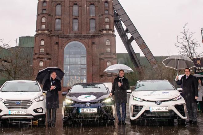 Sie rollten mit drei Wasserstoff-Autos über die geplante Umwelt-Trasse: Bottrops Oberbürgermeister Bernd Tischler (links), Markus Masuth, Vorsitzender der Geschäftsführung RAG Montan Immobilien GmbH, und Essens OB Thomas Kufen vor dem Malakoffturm von Prosper II.