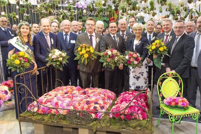 Eine Menschengruppe inmitten von Blumendekorationen