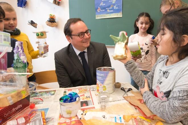 Oberbürgermeister Kufen sitzt mit bastelnden Kindern zusammen
