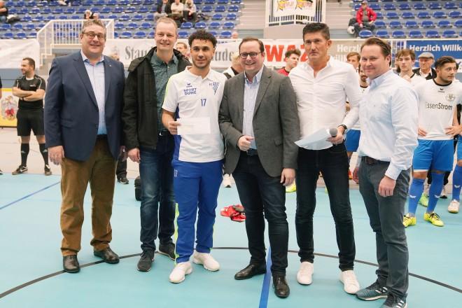 Sechs Männer stehen in einer Sporthalle