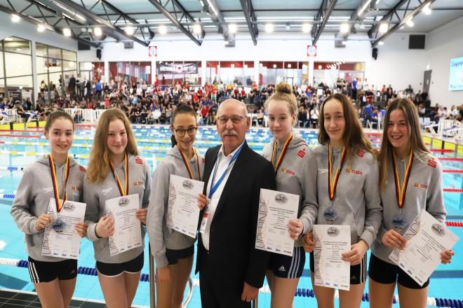 Ein Mann mit sechs jungen Schwimmerinnen in einer Schwimmhalle
