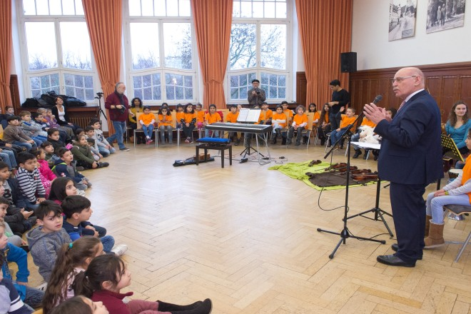 Ein Mann spricht in einem Raum zu einer großen Gruppe von Kindern