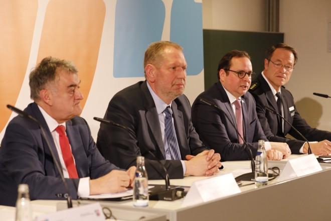 Vier Männer sitzen an einer Rednerbank. Einer ergreift das Wort.