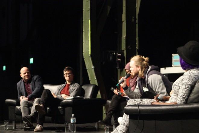 Fünf Menschen sitzen auf Sofas und reden