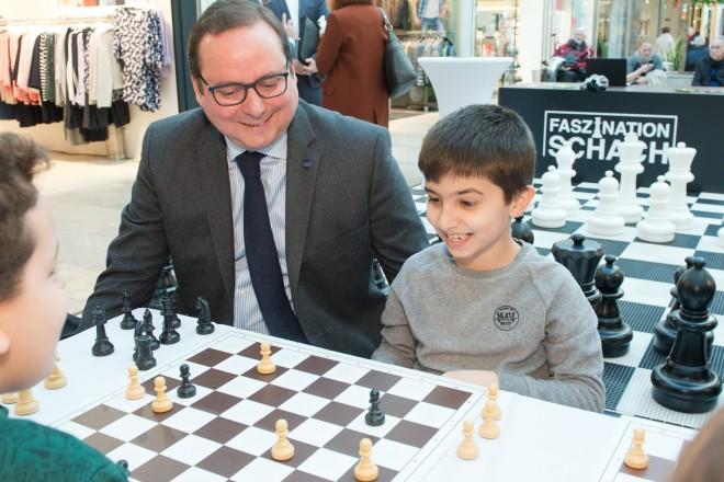 Oberbürgermeister Thomas Kufen mit zwei Jungen beim Schachspielen.