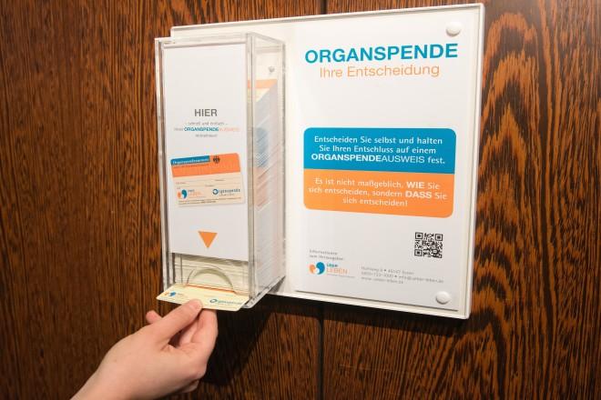 Foto: Eine Hand entnimmt einen Organspenderausweis aus einer Spenderbox