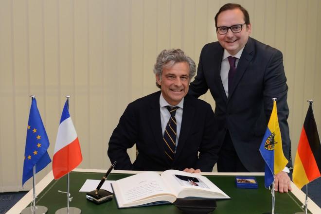 Der Bankier Philippe Oddo trägt sich im Beisein von Oberbürgermeister Thomas Kufen in das Gästebuch des Oberbürgermeisters ein