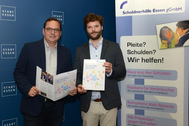 Philipp Hennen, Geschäftsführer der Schuldnerhilfe, übergibt den Jahresbericht der Schuldnerhilfe Essen an Oberbürgermeister Thomas Kufen