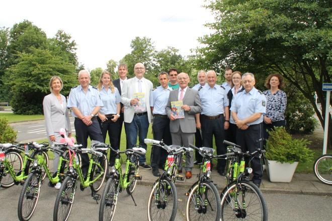 Foto: Erster Bürgermeister Rudolf Jelinek (mittig) überreicht 15 neue Kinderfahrräder an die Verkehrswacht Essen e.V.