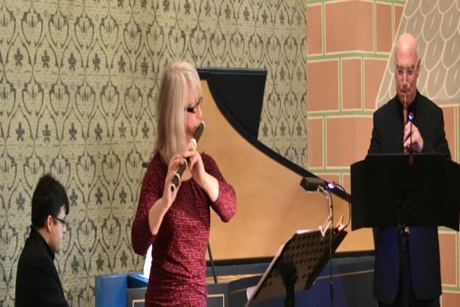 Foto, Die Flötistin Eva Morsbach steht links vom Klavier und der Oboist Alessandro Piqué steht recht vom Klavier. Beide spielen Instrumente.