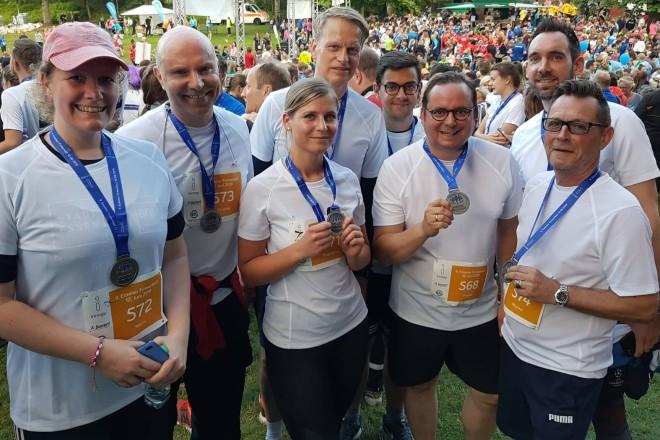 Team des Oberbürgermeister-Büros beim Essener Firmenlauf 2019 nach der Zielankunft. Acht Menschen in Sportkleidung tragen Medaillen um den Hals und lächeln in die Kamera. Im Hintergrund in einer Parklandschaft viele weitere Menschen.