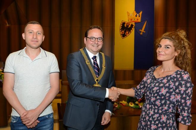 27. Einbürgerungsfeier Oberbürgermeister Thomas Kufen beglückwünscht Pempe Öktem und Hani Jadku.