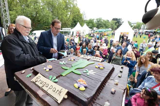 Grugapark-Geburtstagfest. Oberbürgermeister Thomas Kufen schneidet gemeinsam mit Hans-Peter Huch die Geburtstagstorte an
