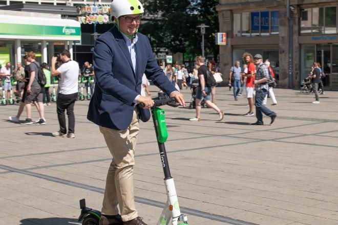 Foto: Oberbürgermeister Thomas Kufen testet einen der mietbaren E-Scooter.