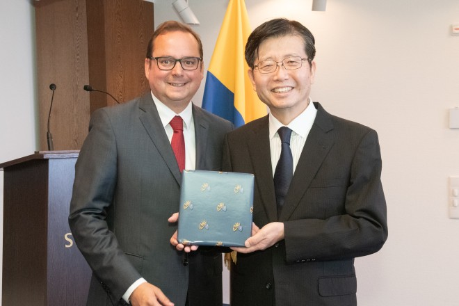 Foto: Prof. Dr. Ing. Yoshihito Ozawa, Vorsitzender der Delegation und Professor an der Fukushima University, nimmt ein Willkommensgeschenk entgegen.