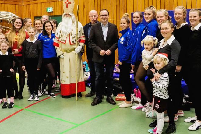 Foto: Oberbürgermeister Thomas Kufen (mitte) mit Horst Littmann (links daneben), Vorsitzender des KSV und Jörg Ostermann (links außen), 2. Vorsitzender des KSV, sowie einigen Turnerinnen beim Nikolausturnen des KSV.