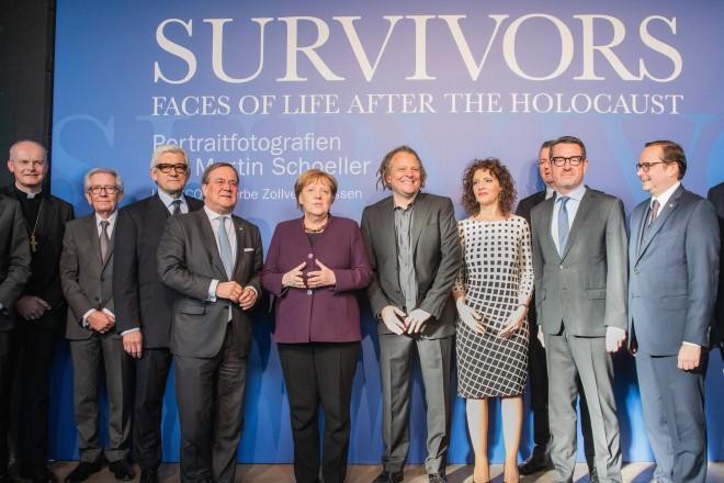 """Foto: Gruppenfoto von politischen und gesellschaftlichen Vertretern vor einer Blauen Wand mit der Überschrift """"Survivors""""."""