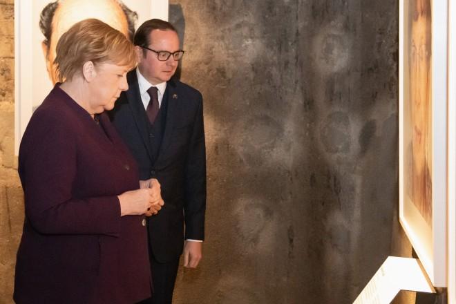 """Foto: Oberbürgermeister Thomas Kufen mit Bundeskanzlerin Angela Merkel in der Ausstellung """"Survivors"""" auf Zeche Zollverein."""