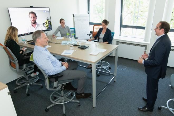Foto: Web-Konferenz mit Tim Böker, Marketing-Experte. Oberbürgermeister Thomas Kufen (rechts), Andre Boschem von der EWG (vorne) und Svenja Krämer von der EMG (mitte) tauschen sich über Videoschalte mit Herrn Böker aus.