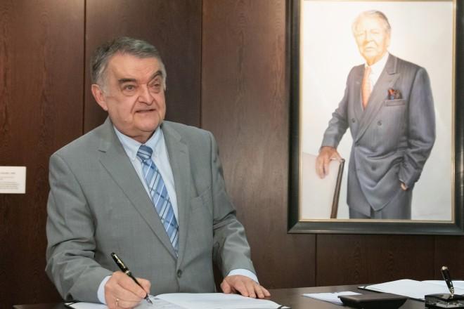 Foto: Ein Mann steht an einem Tisch und unterschreibt ein Dokument.