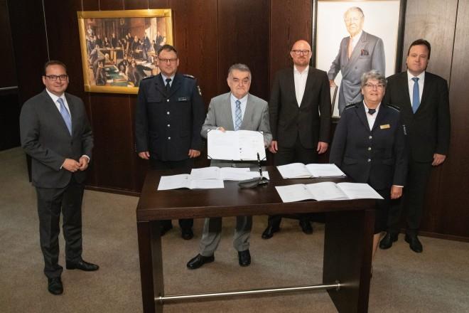 Foto: Sechs Menschen stehen hinter einem Tisch einer hält ein Dokument offen, Richtung Kamera.