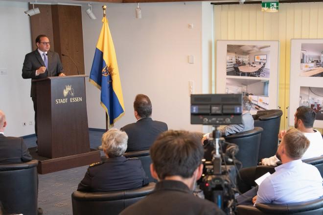 Foto: Ein Mann steht an einer Kanzel und redet in zwei Mikrofone. Vor ihm sitzen viele Journalisten udn Kameraleute.