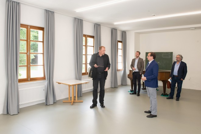 Foto: Vier Personen stehen in einem Raum mit Fenstern, hinter ihnen ein Klavier, ein Tisch und eine Schultafel.