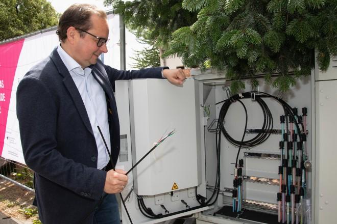 Oberbürgermeister Thomas Kufen begutachtet die neue Glasfasertechnik der Breitbandleitung. Moritz Leick, Stadt Essen